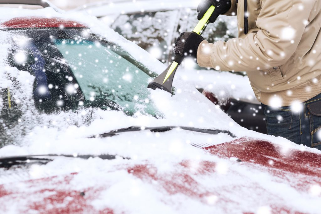 Scraping snow off windshield in the winter