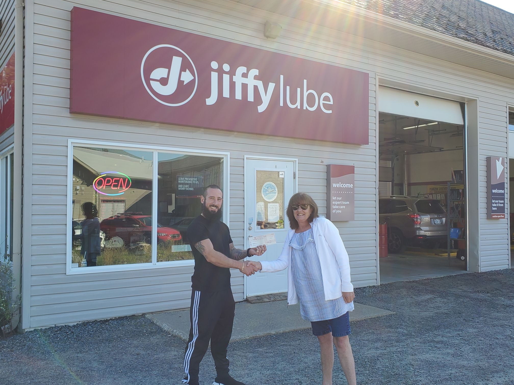 Winner from Jiffy Lube's 20th Anniversary Contest receiving her prize in front of a Jiffy location